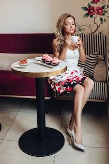 Miła kobieta siedzi w dużej jasnej kuchni