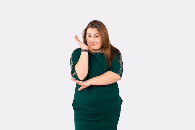 Miła kobieta stojąca na nogach z długimi włosami uniosła prawą rękę i z uśmiechem patrzyła na ubrania w dużym rozmiarze