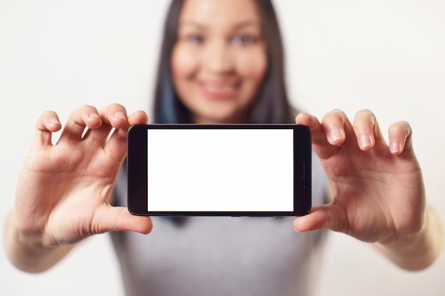 Miła kobieta trzyma smartfon z pustym białym ekranem z dwiema rękami poziomo i uśmiecha się