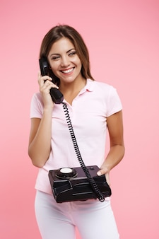 Miła kobieta w jasnym stroju swobodnego wykonywania połączeń telefonicznych i uśmiechnięta