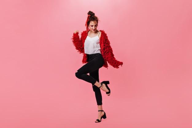 Miła kobieta w wełnianej kurtce i czarnych spodniach tańczy na różowo