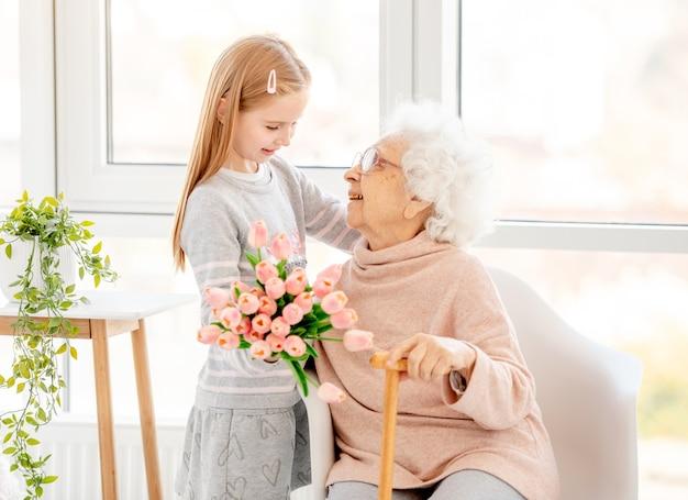 Miła mała dziewczynka prezentuje bukiet swojej babci w jasnym pokoju