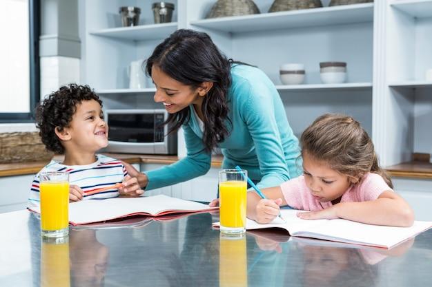 Miła matka pomaga jej dzieciom odrabianiu lekcji