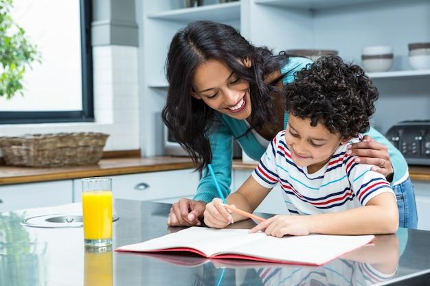 Miła matka pomaga jej synowi robi pracie domowej