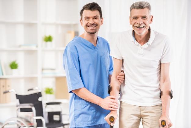 Miła męska pielęgniarka pomaga starszemu pacjentowi o szczudłach.