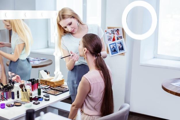 Miła miła kobieta stojąca obok klienta podczas nakładania makijażu na twarz