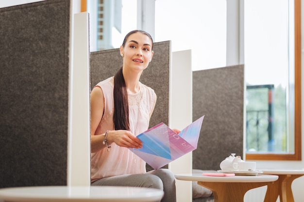 Miła miła kobieta trzyma magazyn będąc w salonie piękności