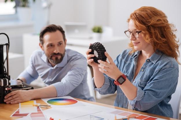 Miła, miła, zachwycona kobieta siedzi ze swoim kolegą przy stole i trzymając wydrukowany przedmiot patrząc na niego