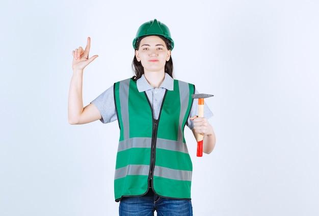 Miła młoda brygadzistka skierowana w górę, trzymając młotek przed szarą ścianą