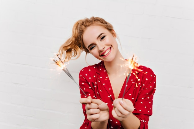 Miła młoda dama w czerwonym stroju trzymająca bengalskie światła. kryty zdjęcie podekscytowanej dziewczyny z falowanymi blond włosami z okazji nowego roku.