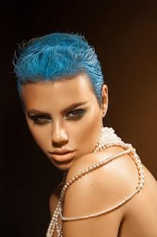 Miła, młoda, dorosła kobieta z krótką niebieską fryzurą i perłami na szyi