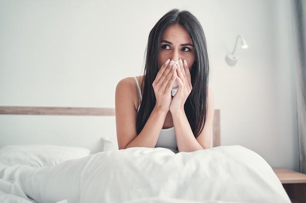 Miła młoda kobieta siedzi w domu pod kocem i trzyma serwetkę w obu rękach