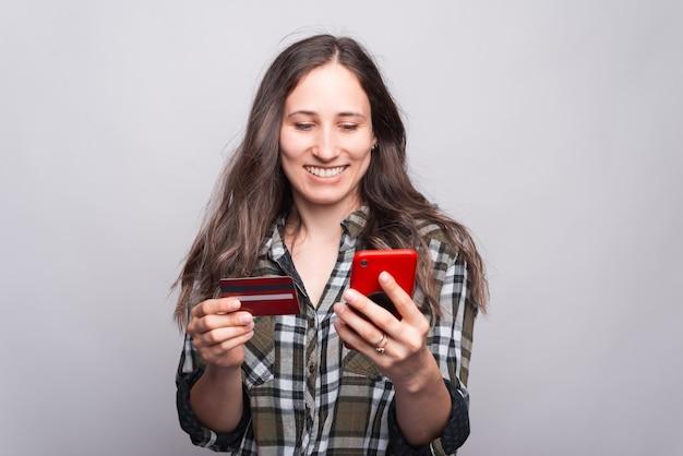 Miła młoda kobieta trzyma telefon, aw drugiej ręce kartę kredytową w pobliżu szarej ściany