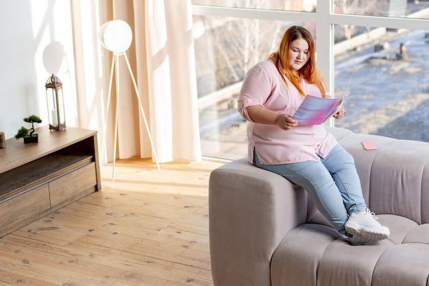 Miła młoda kobieta trzymająca magazyn kosmetyczny i czytająca o nowych trendach