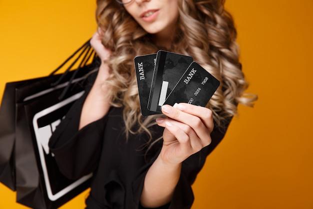 Miła młoda kobieta w czarnej sukni i przezroczystych okularach z czarnymi kartami kredytowymi