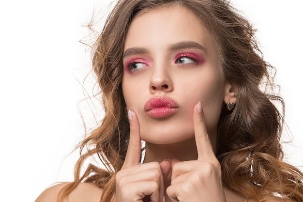 Miła młoda kobieta z długimi falowanymi jedwabistymi włosami, naturalny makijaż, patrząc na kamery