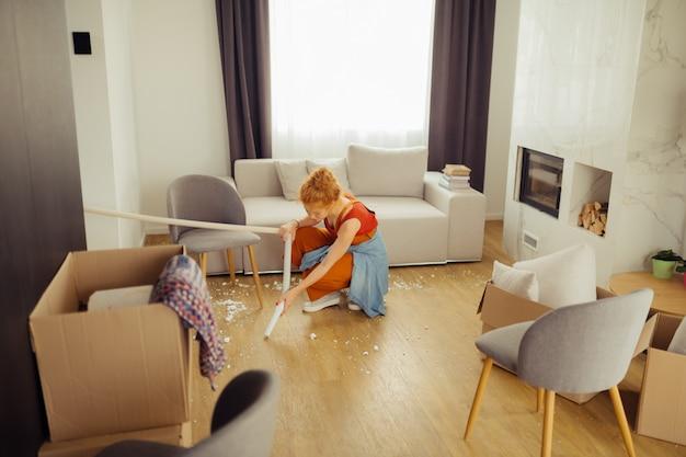 Miła młoda kobieta za pomocą odkurzacza w swoim domu