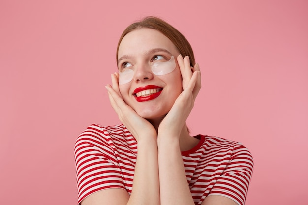 Miła młoda rudowłosa dama z czerwonymi ustami, w czerwonej koszulce w paski, bardzo zadowolona z nowych łat po cieniach pod oczami, dotyka palcami jego twarzy stands.