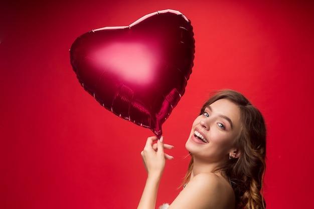Miła młoda uśmiechnięta kobieta z długimi falowanymi jedwabistymi włosami, naturalny makijaż z balonem w kształcie serca na białym tle na czerwonej ścianie. koncepcja walentynki