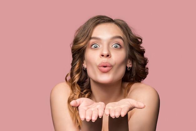 Miła młoda uśmiechnięta kobieta z długimi falującymi jedwabistymi włosami, naturalny makijaż z pocałunkiem na różowej ścianie. model o świeżej błyszczącej skórze i naturalnym makijażu. emocje ludzi