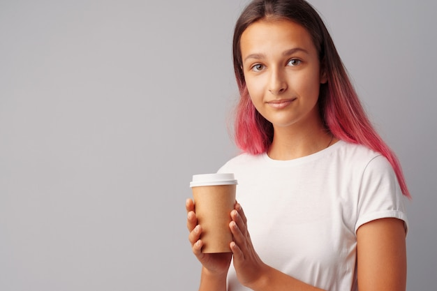 Miła nastolatka dziewczyna trzyma kubek kawy