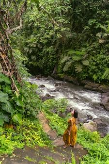 Miła osoba płci żeńskiej stojąca w półpozycji i słuchająca dźwięków płynącej rzeki