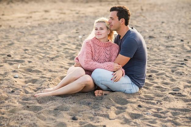 Miła para w związku siadając na plaży w wakacje. słodycz z kaukaskim młodym mężczyzną i kobietą. blond i biała skóra cieszą się miłością i wiekiem. koncepcja lato