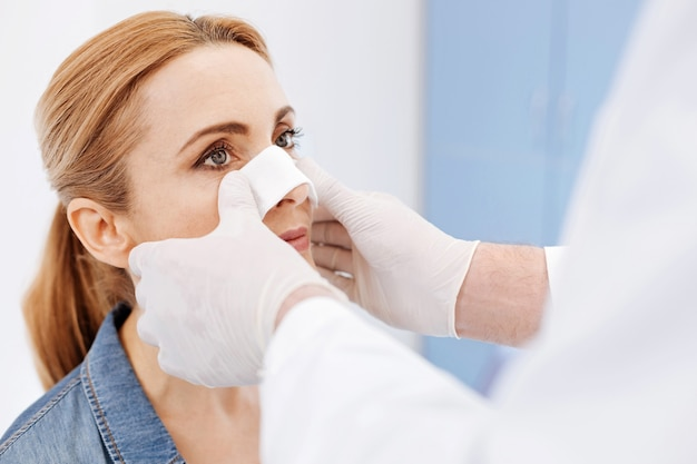 Miła, poważna, atrakcyjna kobieta odwiedzająca szpital i przechodząca operację plastyczną, chcąca mieć idealny nos