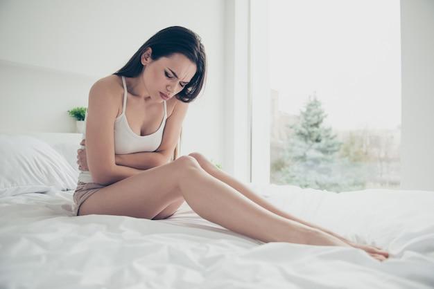 Miła pozytywna dziewczyna pozuje w swoim łóżku