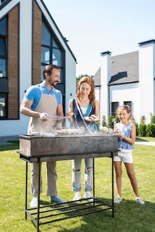 Miła radosna rodzina stojąca razem podczas przygotowywania potraw na grillu