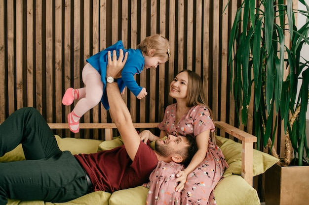 Miła rodzina leży na kanapie i dobrze się bawi w weekend.