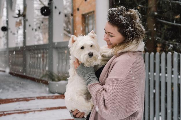 Miła roześmiana dziewczyna przytulająca uroczego białego psa z zabawnymi słodkimi emocjami. west highland white terrier. koncepcja adopcji.