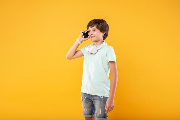 Miła rozmowa. szczęśliwy ciemnowłosy chłopak uśmiecha się podczas rozmowy przez telefon