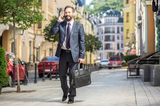 Miła rozmowa. wesoły biznesmen uśmiechający się spaceru do pracy podczas rozmowy telefonicznej