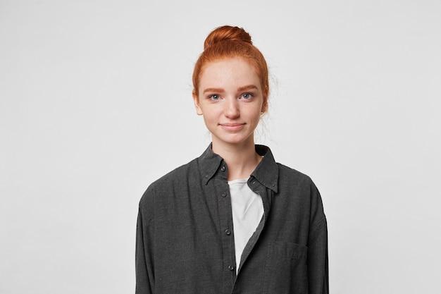 Miła rudowłosa dziewczyna z kokem na głowie ubrana w prostą, oversizową czarną koszulę