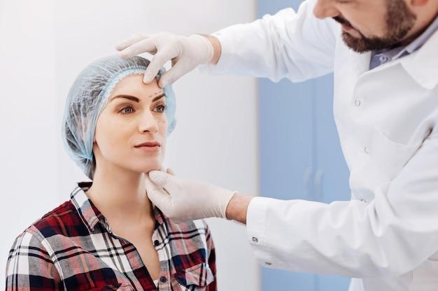 Miła, sympatyczna, atrakcyjna kobieta siedząca na krześle w czapce i po konsultacji z chirurgiem plastycznym
