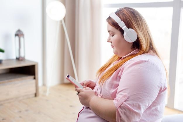 Miła sympatyczna kobieta trzymająca smartfona podczas wybierania utworu do odtworzenia