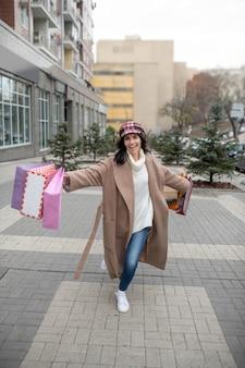 Miła szczęśliwa kobieta trzyma wiele toreb na zakupy, idąc do domu po zakupach