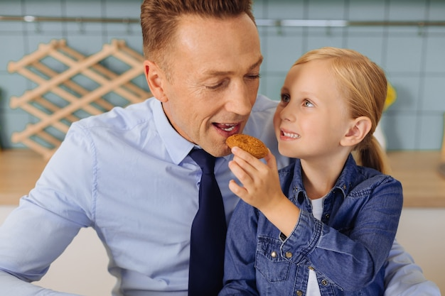 Miła, zachwycona młoda dziewczyna trzyma ciastko i podaje je swojemu ojcu