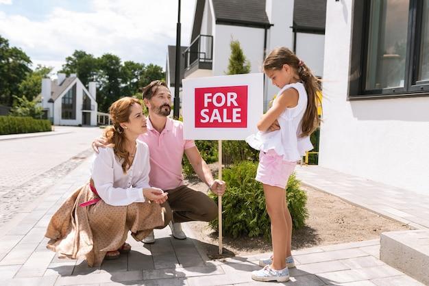 Miła zdenerwowana dziewczyna stojąca przed rodzicami, nie lubiąca nowego domu