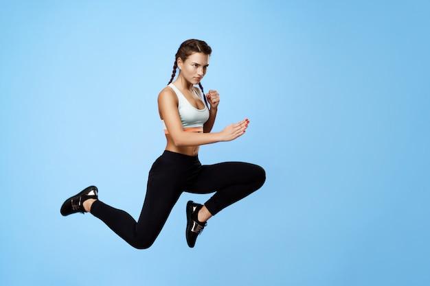 Miła, zmotywowana kobieta fitness w chłodnym, stylowym stroju sportowym, skacząca wysoko z rękami odwracającymi wzrok
