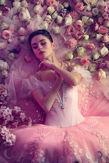 Milczenie jest złotem. widok z góry piękna młoda kobieta w różowej spódniczce baletowej otoczonej kwiatami. wiosenny nastrój i delikatność w koralowym świetle. koncepcja wiosny, kwitnienia i przebudzenia przyrody.