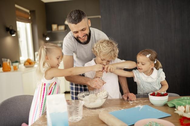 Miłe aktywne dzieci, które chcą trzymać trzepaczkę
