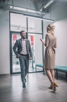 Miłe spotkanie. radosny biznesowy brodaty mężczyzna w szarym garniturze idący w kierunku szczupłej kobiety w sukience na wysokich obcasach z dokumentami