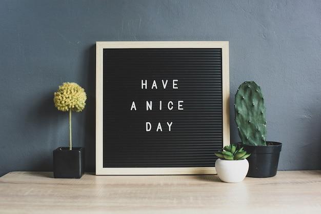 Miłego dnia cytat na tablicy z kaktusem, soczystą i dekoracyjną rośliną na drewnianym stole