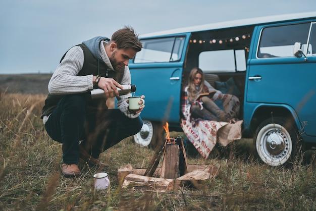 Miłego dnia. piękna młoda kobieta czyta książkę, podczas gdy jej chłopak nalewa drinka przy ognisku