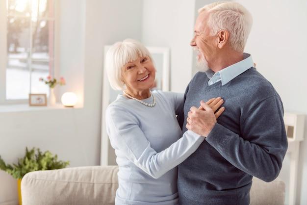 Miłego tańca. szczęśliwa urocza starsza kobieta uśmiecha się tańcząc walca z mężem w salonie