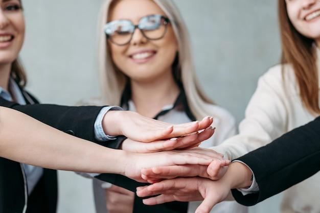 Milenialsi odnoszący sukcesy w biznesie. jedność pracy zespołowej w firmie. żeński zespół profesjonalistów złożył ręce.