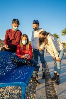 Milenijni przyjaciele korzystający ze smartfonów w masce ochronnej na fali covid. zmartwieni faceci i dziewczęta oglądając wiadomości na smartfonie mobilnym. grupa podróżnych pozostaje w kontakcie podczas pandemii na wakacjach