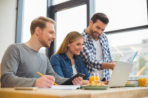 Mili, pozytywni, inteligentni ludzie siedzą razem i dyskutują o swoim projekcie podczas pracy w zespole